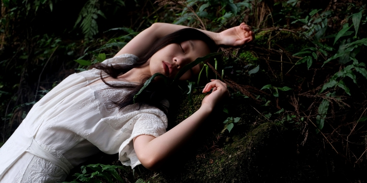 Woman in white dress sleeping against mossy stone