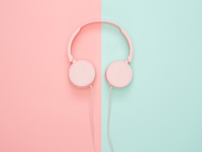 Pale pink headphones on background of coral and seafoam green