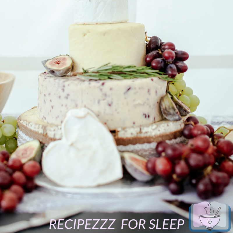 Stack of cheeses with fruit. One cheese in a heart shape